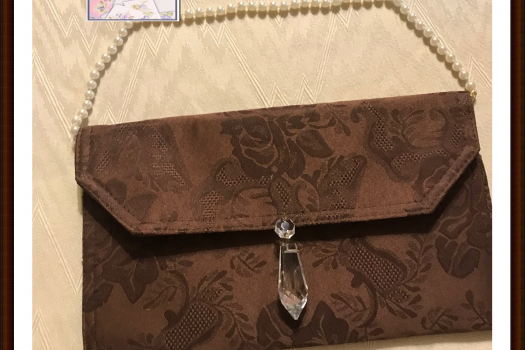 Brwon purse with crystal purse charm and peal strap